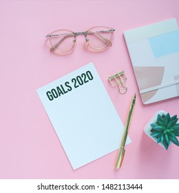 Goals 2020 on flat lay photo of colorful workspace desk with card, eyeglasses and notebook with copy space background, minimal style and mockup concept