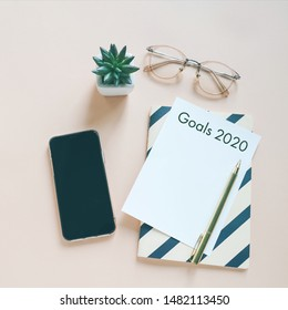 Goals 2020 on flat lay photo of workspace desk with smartphone, card and notebook with copy space background, minimal style and mockup concept