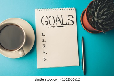 GOALS concept. Notepad with checklist, cup of coffee and pen on blue background, top view