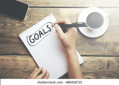 Goals memo written on a notebook with woman hand pen