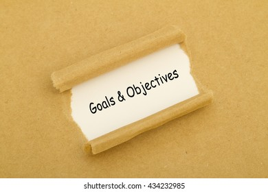 Goals and Objectives words written under torn paper.
