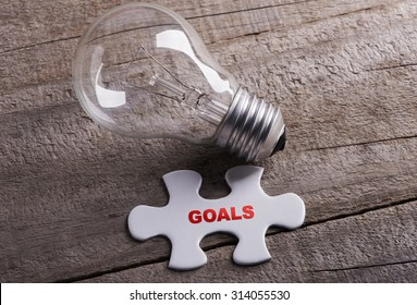 Goals with piece of jigsaw and bulb on wooden background
