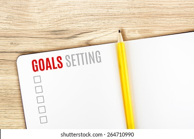 Goals Setting word on notebook lay on wood table,Template mock up for adding your goal.