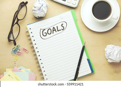 goals text on notebook with calculator and coffe on brown background