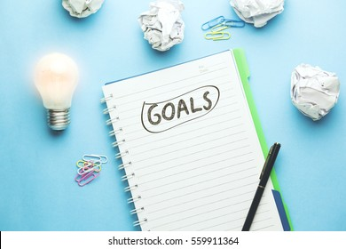 goals text on notebook with idea on blue background