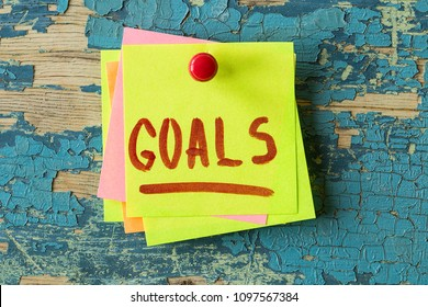 GOALS text written on sticky note on rustic wooden background. Motivational quotes