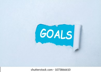 Goals written under tear folded paper, blue and white.
