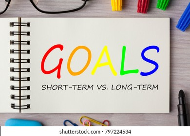 GOALS,SHORT-TERM VS. LONG-TERM written in notebook on wooden desk with marker pen and glasses. Top view.