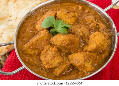 Goan Pork Vindaloo - Indian pork curry with naan bread. Traditional cuisine from Goa.