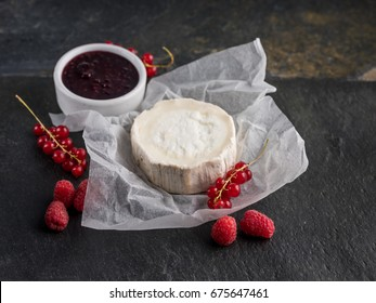 Goat cheese eating in white paper on dark stone background with berries and fruit jam, big size resolution. Food banner for text or design.
