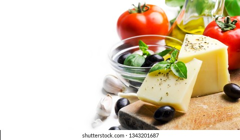 Goat cheese, olives, olive oil, tomato, garlic, basil and spices on wooden cutting board isolated on white background. Food ingredients for italian pizza recipe. Mediterranean cuisine concept.
