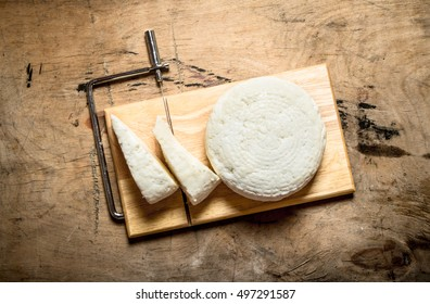 Goat cheese on a cutting Board. On a wooden table.