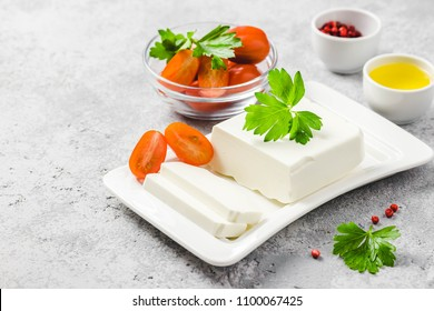 Goat cheese on plate with tomatoes, herbs, olive oil and spices. Selective focus, space for text.