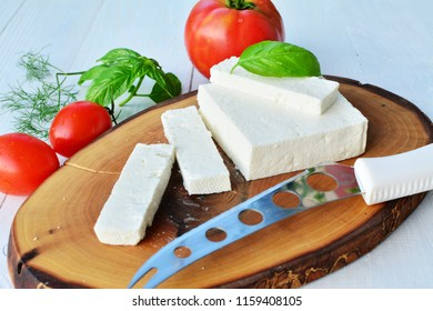 Goat cheese on wooden board with tomatoes and herbs