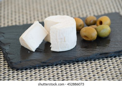 Goat cheese sliced and olives on a black plate.