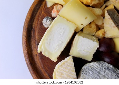 Goat and cow cheese on a round board on a white background close-up, selective focus.