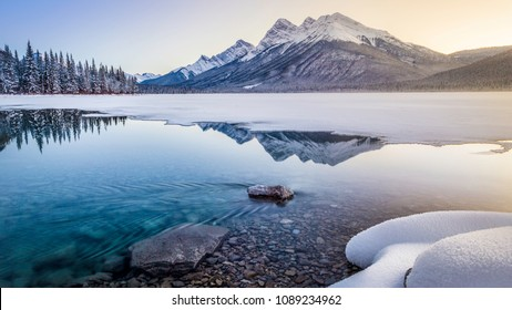 Goat mountains in kananaskis country with lake reflection in winter