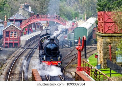 GOATHALAND, ENGLAND - MAY 1, 2018: A vintage passenger steam train with carriages and locomotive 926 leaving Goathland Station on the way to Whitby on the North York Moors Railway.