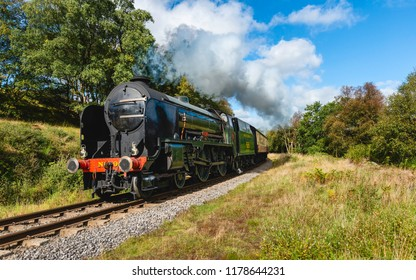 GOATHLAND, UK - SEPTEMBER 12, 2018:  A vintage steam train ploughs through the North York Moors on an autumn morning on September 12, 2018 near Goathland, Yorkshire, UK.