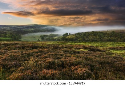 Goathland, Yorkshire, UK. Dawn mist over the North York Moors National Park shot in autumn (fall) when the heather is in full bloom near the village of Goathland, north Yorkshire, UK.