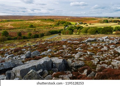 Goathland, Yorkshire, UK. Rolling landscape of the North York Moors with heather, rocks, and farmland on a bright day in autumn, Goathland, Yorkshire, UK.