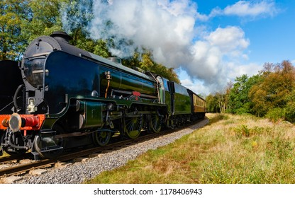 Goathland, Yorkshire, UK. A vintage steam train ploughs through the North York Moors on an autumn morning near Goathland, Yorkshire, UK.
