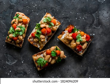 Goats cheese crostini with garlicky beans on a dark background, top view. Delicious tapas, appetizers                              - Shutterstock ID 1824096209