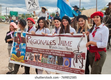 """GOBERNADOR COSTA, ARGENTINA - 4 FEBRUARY, 2017: Girls holding a poster at the regional annual festival, fair """"Regionales Jaime"""" in province of Chubut in suburb of village Gobernador Costa."""