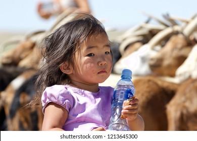 GOBI DESERT - AUGUST 2018: portrait of a beautiful Mongolian little girl playing with a bottle of mineral water, Gobi desert, Mongolia