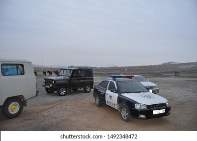 """GOBI DESERT, MONGOLIA - CIRCA OCTOBER 2007: Police car, Russian van, Jeep, horses, and outhouse in front of """"hotel"""" in Gobi desert in Mongolia."""