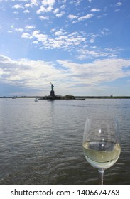 Goblet glass of white wine rests in foreground with Statue of Liberty in background as seen from Hudson River. Early evening or dusk view. Sunlight sparkles on water.