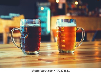 Goblets light and dark beer on a wooden table on a pub background. Assorted alcohol in a Flight Ready for Tasting