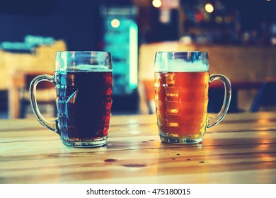 Goblets light and dark beer on a wooden table on a pub background. Assorted alcohol in a Flight Ready for Tasting. Blue toned