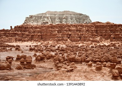 Goblin valley desert rocks, huge white rock behind, red rocks in front