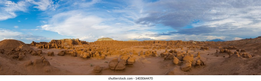 """Goblins"""" in Goblin's Valley State Park in Utah near Green River. In the photo are various goblin formations made out of Entrada Sandstone. Clear blue skies contrast the red rocks and white clouds."""