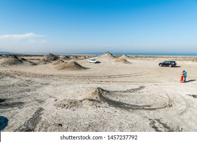 Gobustan, Azerbaijan - May 1, 2019.  Tourists among cones of gryphon mud volcanoes in Gobustan, Azerbaijan, with cars.