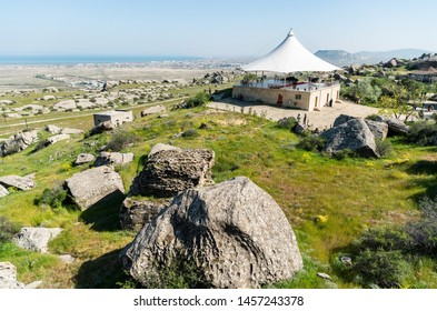 Gobustan, Azerbaijan - May 1, 2019. Landscape in Gobustan national park, with pavilion, people and Gobustan settlement in the distance.