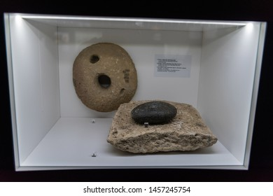 Gobustan, Azerbaijan - May 1, 2019. Display featuring quern stone used for grinding grains, at the Gobustan Museum in Azerbaijan.