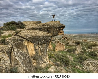 GOBUSTAN, AZERBAIJAN - November 2016: Gobustan National park, rocky mountains landscape, woman on the cliff in Gobustan, Azerbaijan