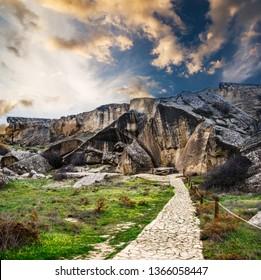 Gobustan national park ancient rocks, rock path and mountains near Baku in Azerbaijan at sunset.