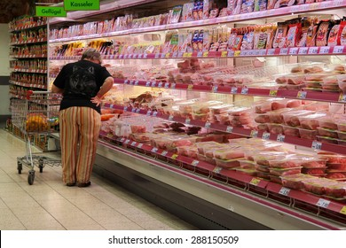 GOCH, GERMANY - MAY 6: Customer selecting packaged meat in refrigerated section of a Kaufland hypermarket. Photo taken on May 6, 2015 in Goch, Germany