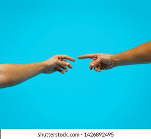God and Adams hands. Creation of human. Genesis. Touch of god. Spirituality. A section of Michelangelo's fresco Sistine Chapel ceiling. Close-up of man hands on blue background isolated