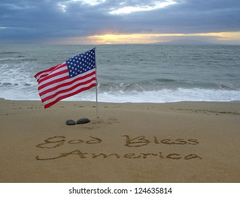 God Bless America handwritten in the sand with an American flag blowing in the breeze