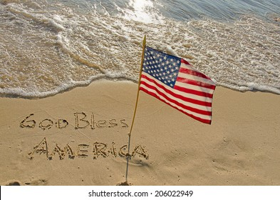 God Bless America written in beach sand with American flag