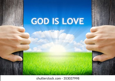 """God is Love. Hand opening an old wooden door and found wording """"God is Love"""" over green field and bright blue Sky Sunrise."""