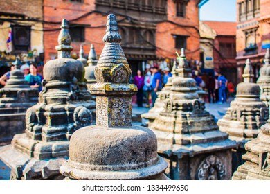 God stupas at the Swayambhunath Stupa, also known as the Monkey temple - the Buddhist temple and the village center of the outskirts in Kathmandu, Nepal. Blurred people walking on the background.