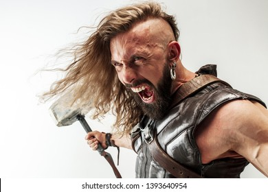 God of thunder. Blonde long hair and muscular male model in leather viking's costume with the big hammer cosplaying isolated on white studio background. Fantasy warrior, antique battle concept.