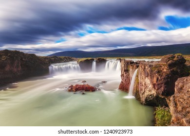 Godafoss (Akureyri) waterfall at sunny day, spectacular landscape of Iceland iconic place with blue cloudy sky, long exposure. Skjalfandafljot river, Norðurland, North of Iceland