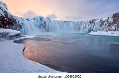 Godafoss frozen waterfall during Winter at sunrise. North Iceland.