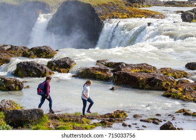 GODAFOSS, ICELAND - JULY 21, 2017. Two young women walk above the rim of Godafoss falls, near Akureyri, Northern Iceland